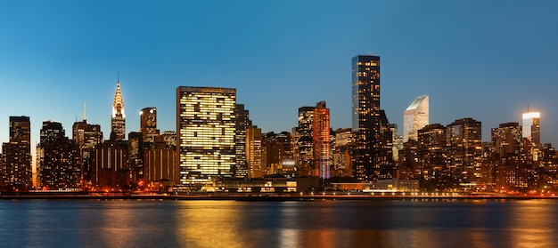 Manhattan. laat in de avond new york city skyline panorama met lichten en reflecties.