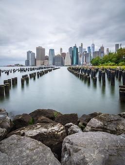 Manhattan skyline met een oude pier op de voorgrond.