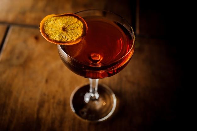 Manhattancocktail versierd met een sinaasappelplak