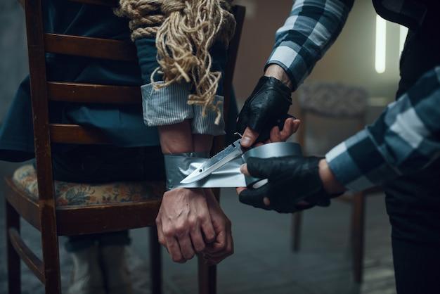 Maniak ontvoerder die de handen van zijn vrouwelijke slachtoffer vastplakt. ontvoering is een ernstige misdaad, gekke mannelijke psychopaat, ontvoeringsgruwel, geweld