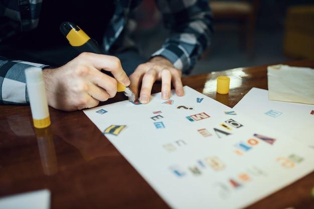 Maniak ontvoerder handen knipt letters uit om tekst samen te stellen. ontvoering is een ernstige misdaad, mannelijke psychopaat, ontvoeringsgruwel