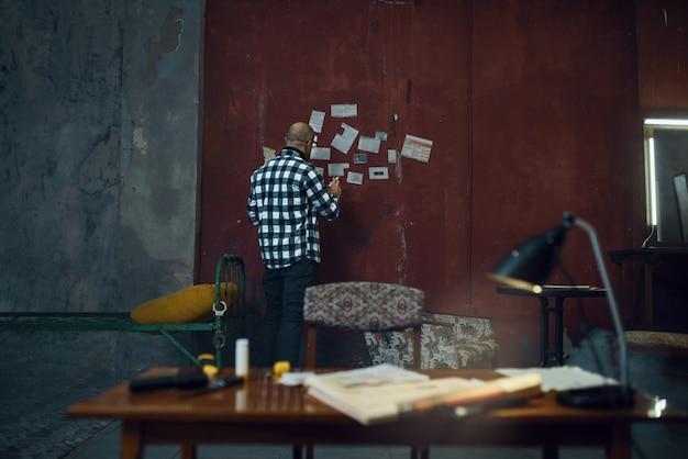 Maniak-ontvoerder kijkt naar de advertenties van zijn slachtoffers. ontvoering is een ernstige misdaad, mannelijke psychopaat, ontvoeringsgruwel