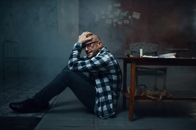 Maniak ontvoerder zittend op de vloer. ontvoering is een ernstige misdaad, gekke mannelijke psychopaat, ontvoeringsgruwel, geweld