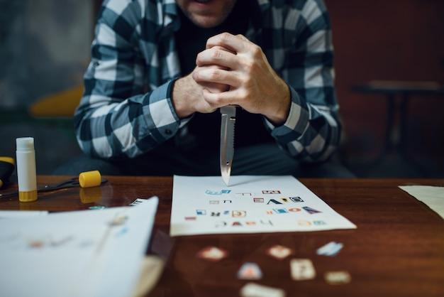 Maniakontvoerder met mes kijkt naar tekst die uit uitgesneden letters bestaat. ontvoering is een ernstig misdrijf, mannelijke psychopaat, ontvoeringsgruwel, geweld