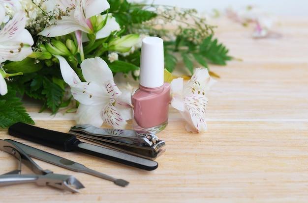 Manicure accessoires: nude nagellak, diamant nagelvijl, nagelriemverwijderaar, tondeuse en nagelduwer. manicure thuis concept. kopieer ruimte.