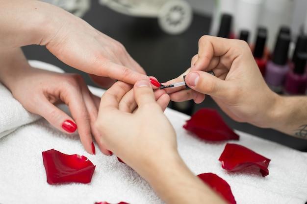 Manicure. close-up van mooie vrouw handen polijsten nagels met rode nagellak in schoonheidssalon.