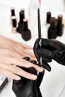 Manicure die kunst op middelvinger doet, die met kunstborstel trekt.