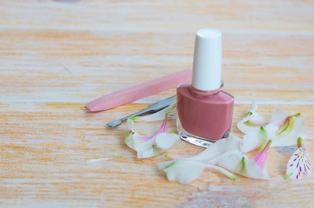 Manicure- en pedicureaccessoires: nude nagellak met bloemblaadjes, steen nagelvijl nagelriemverwijderaar en nagelschuif. kopieer ruimte.