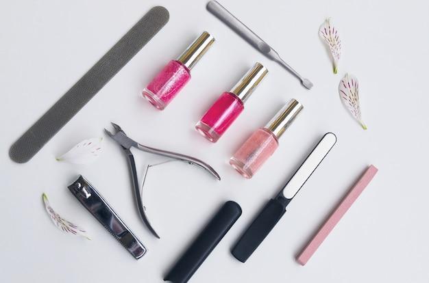 Manicure- en pedicuregereedschappen die meestal in schoonheidssalons worden gebruikt. diamant nagelvijl, steen nagelvijl nagelriemverwijderaar, nagelknipper en drie nagellak in roze toon. plat leggen cosmetica.