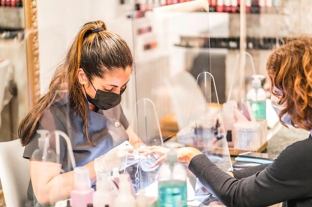 Manicure- en pedicuresalon, coronavirus, covid-19, sociale afstand. de heropening vanwege de pandemie, veiligheidsmaatregelen. detail van een vrouwelijke werknemer achter het beschermende scherm