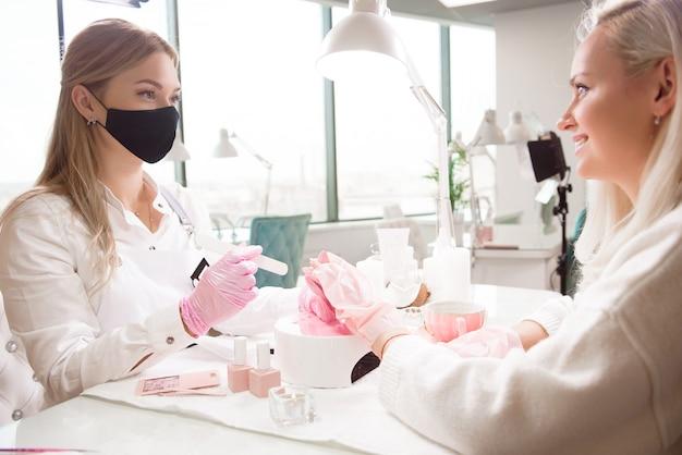 Manicure- en pedicuresalon, covid-19 en sociale afstand. meester in rubberen handschoenen en jonge vrouw cliënt in beschermend masker in schoonheid studio interieur.