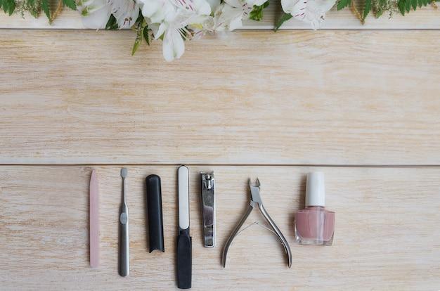 Manicure en pedicuretoebehoren op houten achtergrond met bloemkader. diamant nagelvijl, steenvijl nagelriemverwijderaar, nagelknipper en nude nagellak. ruimte kopiëren.