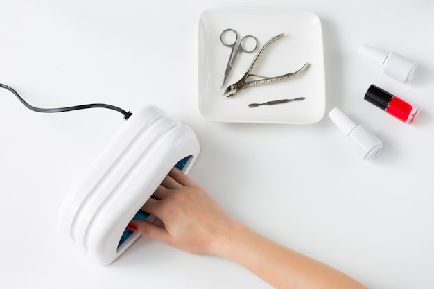 Manicure gereedschap, nagellak, vrouwelijke hand in nagellak drooglamp