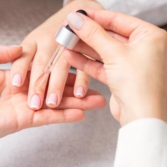 Manicure giet olie op de nagels van de vrouw