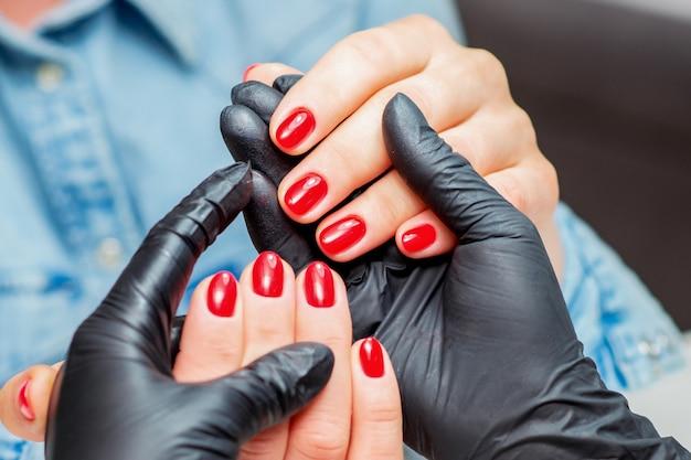 Manicure houdt handen vast met rode nagels van vrouwelijke cliënt close-up.