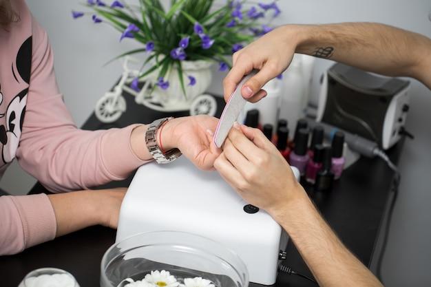 Manicure in schoonheidssalon. selectieve aandacht voor de nagels van de klant
