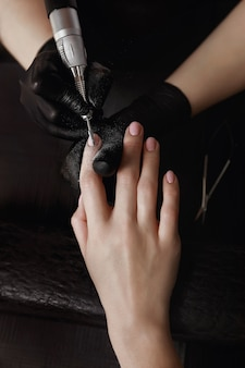 Manicure in zwarte handschoenen, slijpmachine verwijdert oude gel polish. bereidt zich voor op nagelverlenging. spa faciliteiten. manicure kamer.
