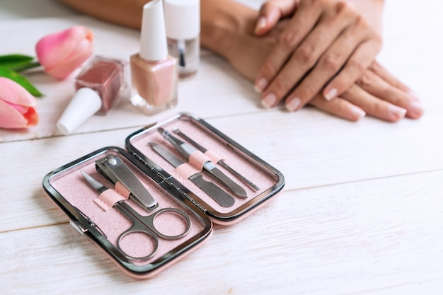 Manicure instrumenten set met nagellak en vrouwenhanden