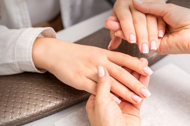 Manicure meester houdt handen van een jonge vrouw met afgewerkte manicure op vingers in een nagelsalon