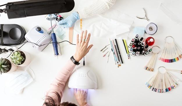 Manicure meester in masker en handschoenen gel polish op de nagels van een cliënt te zetten