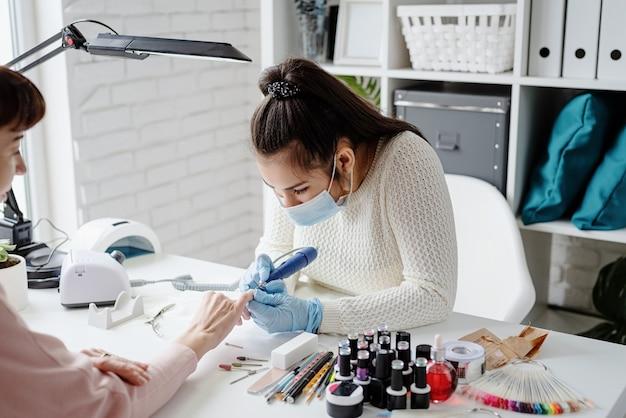 Manicure meester in masker en handschoenen met behulp van een elektrische machine om de nagellak te verwijderen