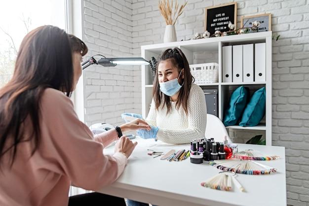 Manicure meester in rubberen handschoenen en masker praten met de klant in schoonheid studio interieur