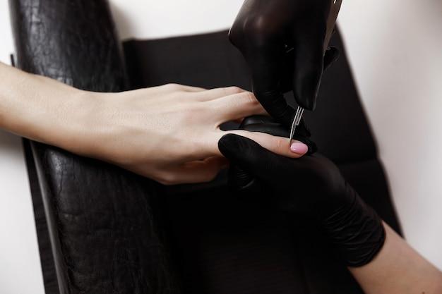 Manicure meester in zwarte handschoenen, schaar, verwijdert nagelriemen. nagel verlenging. spa faciliteiten. manicure kamer.