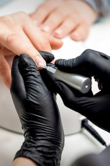 Manicure meester is transparante vernis toe te passen op vrouwelijke nagels in nagelsalon