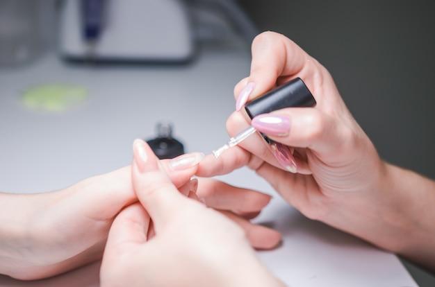 Manicure meester maakt manicure aan de kant van de vrouw