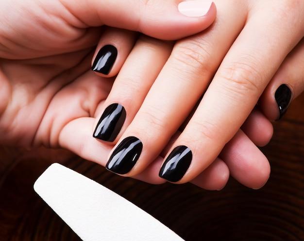 Manicure meester maakt manicure op handen van de vrouw - spa behandeling concept