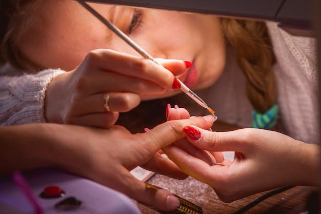 Manicure. meester make nagelverlenging: tekening van witte gel op vrije rand van een nagel