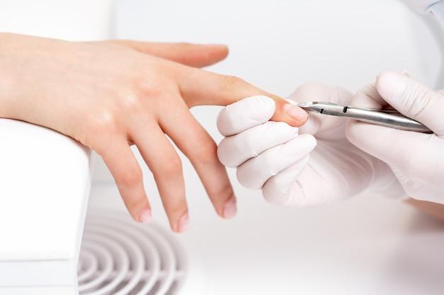 Manicure met manicuresnijder om nagelriem van vrouwelijke nagels in manicuresalon te verwijderen