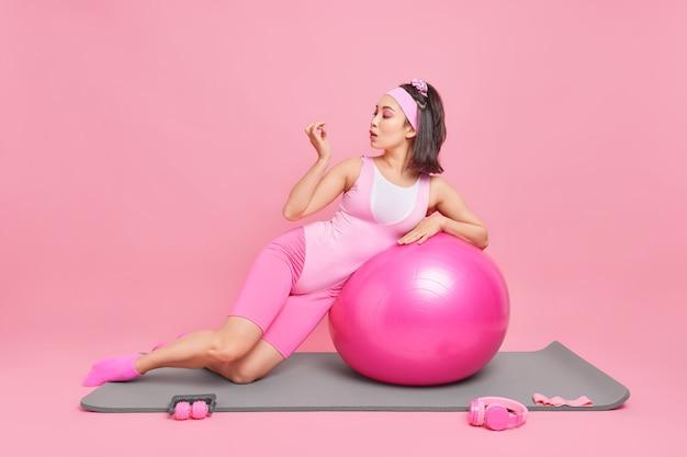 Manicure neemt pauze na fitnesstraining leunt op zwitserse bal poseert op mat indoor gebruikt weerstandsband om spieren te trainen