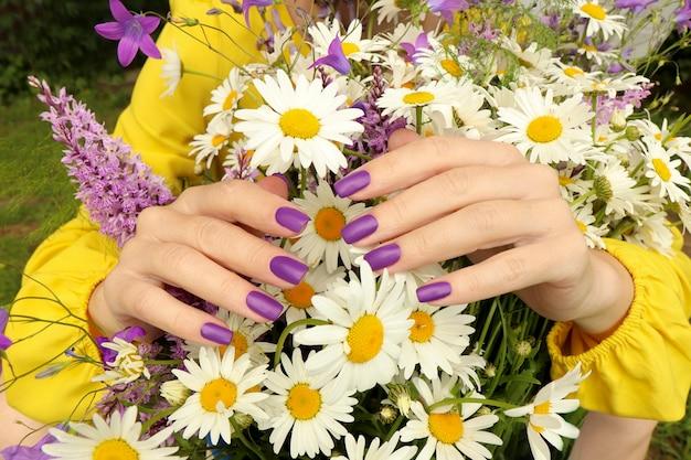 Manicure-ontwerp met een matte lila coating over een boeket madeliefjes.