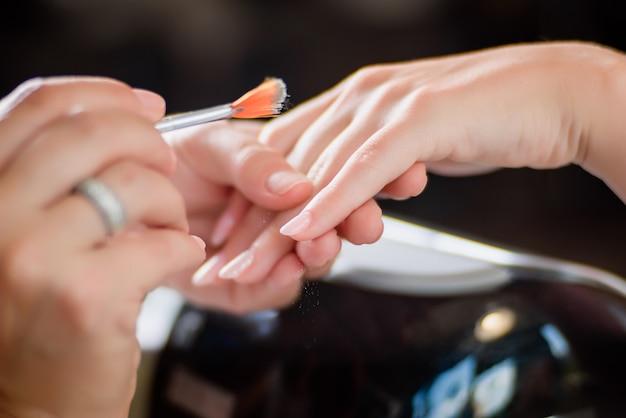 Manicure procedure met patroon en zilveren nagels polish