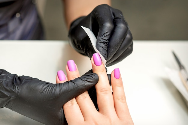Manicure reinigt roze nagellak op vrouwelijke vingernagels na manicure procedure in nagelsalon