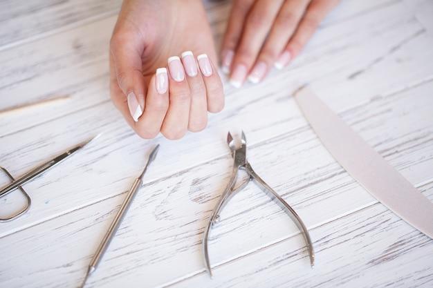 Manicure. sluit omhoog vrouwelijke handen situerend op bureau dichtbij spijkerhulpmiddelen