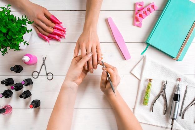 Manicure voor de cliëntclose-up van de handen van een manicure en cliënt op een houten achtergrond