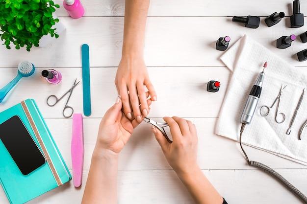 Manicure voor de klant. close-up van de handen van een manicure en een cliënt op een houten achtergrond