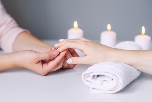 Manicurehanden die massage doen aan de handen van de vrouwelijke cliënt.