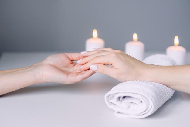 Manicurehanden die massage van de handen van de vrouwelijke cliënt doen. vrouwenhand die manicureprocedure ontvangen.