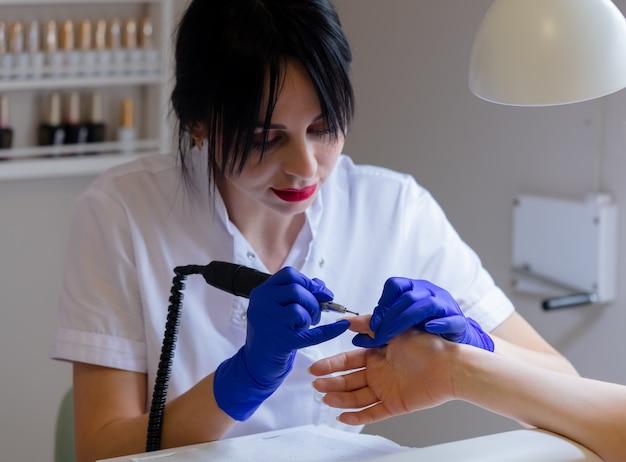Manicuremeester die een machine gebruikt om de nagels schoon te maken