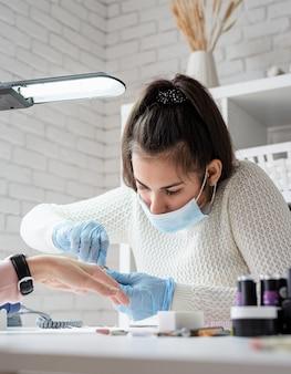 Manicuremeester die een tang gebruikt om manicure aan een cliënt te maken
