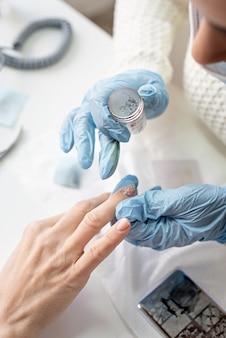 Manicuremeester in masker en handschoenen die aan de cliënt stempelen