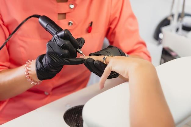 Manicuremeester in zwarte rubberen handschoenen reinigt nagelriemen op cliëntnagels