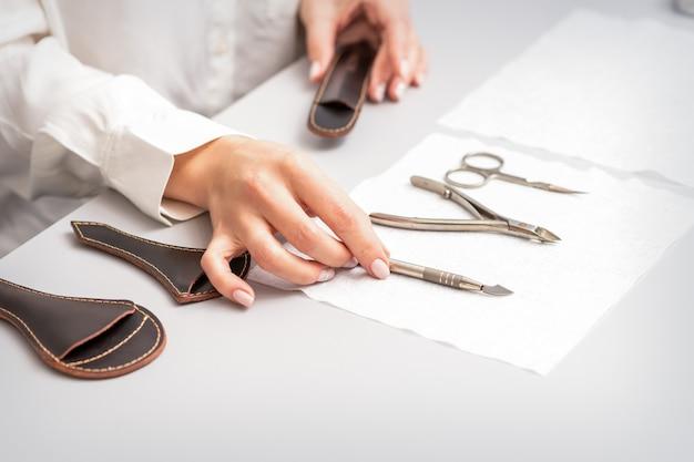 Manicuremeester legt manicureset op een handdoek aan de tafel in een nagelsalon