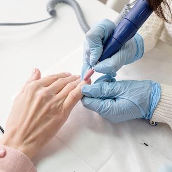 Manicuremeester met behulp van een elektrische machine om de nagels te polijsten tijdens manicure in de salon