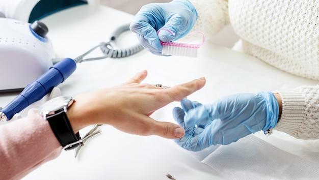 Manicuremeester met een borstel om het stof te vegen na het verwijderen van gellak
