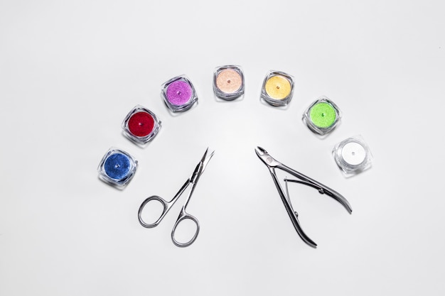 Manicureschaar en nagelknipper omringd door multi-gekleurde pailletten manicure