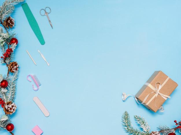Manicureset met een cadeau en versierd met ballen sparren tak op een blauw